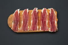 Sliced jamon Serrano or Iberico on cutting wooden board. Traditional spanish hamon on dark wooden background, top view. Flat lay, from above Stock Photography