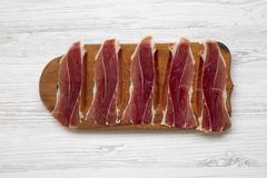 Sliced jamon Serrano or Iberico on cutting wooden board. Traditional spanish hamon on white wooden background, stock photo