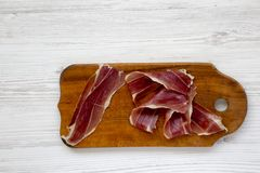 Sliced jamon Serrano or Iberico on cutting wooden board. Traditional spanish hamon on white wooden background, top view. royalty free stock photo