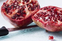 Sliced juicy pomegranate with knife Stock Images