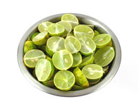Sliced key limes in stainless steel bowl Stock Image