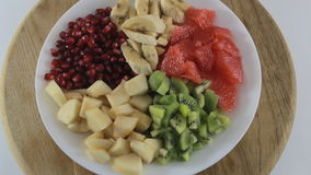 Sliced kiwi, banana, grapefruit, pear and pomegranate rotating on a white plate. Ingredients for fruit salad stock video footage