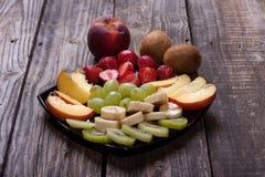 Sliced kiwi, banana, strawberry, green grapes and nectarine lyin. G on a black plate Stock Photo