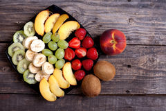 Sliced kiwi, banana, strawberry, green grapes and nectarine lyin. G on a black plate. Top view, old gray boards as background Royalty Free Stock Image