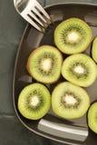 Sliced kiwi on a black plate Stock Photo