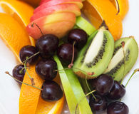Sliced kiwi with cherry and orange and apple. Fruits Stock Photos