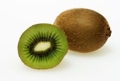 Sliced kiwi fruit. Two Kiwi fruit one cut in half revealing the succulent green pulp and seeds royalty free stock images