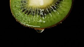 Sliced kiwi fruit. S with drop of juice falling from it in slow motion. Closeup macro shot. Fresh berry and fruit series stock video
