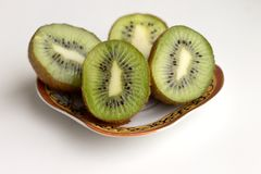 Sliced kiwi fruits lie on a saucer stock image