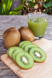 Sliced kiwi and juice on aged wood in garden Stock Photo