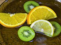 Sliced Kiwi Lemon Orange in water closeup Stock Images