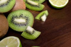 Sliced kiwi with lime on a dark brown wooden table. Sliced kiwi with lime on a dark brown wooden table stock photo
