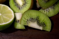 Sliced kiwi with lime on a dark brown wooden table. Sliced kiwi with lime on a dark brown wooden table royalty free stock image