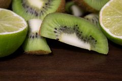 Sliced kiwi with lime on a dark brown wooden table. Sliced kiwi with lime on a dark brown wooden table royalty free stock photography
