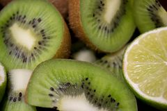 Sliced kiwi with lime on a dark brown wooden table. Sliced kiwi with lime on a dark brown wooden table stock images