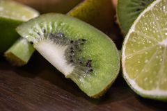 Sliced kiwi with lime on a dark brown wooden table. Sliced kiwi with lime on a dark brown wooden table stock photos