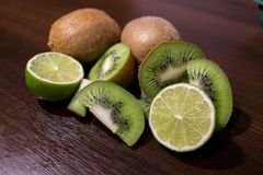 Sliced kiwi with lime on a dark brown wooden table. Sliced kiwi with lime on a dark brown wooden table Royalty Free Stock Photo