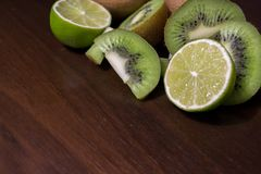 Sliced kiwi with lime on a dark brown wooden table. Sliced kiwi with lime on a dark brown wooden table royalty free stock images
