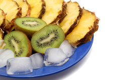 Sliced kiwi and pineapple with ice on a blue plate. Stock Photos