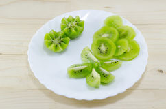 Sliced kiwi placed on a white plate Stock Photos