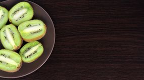 Sliced kiwi on a plate, on a dark background royalty free stock photography