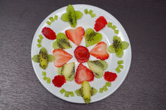 Sliced kiwi and strawberries lying in neatly placed pattern on white plate, as senn from above Royalty Free Stock Images