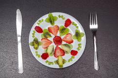 Sliced kiwi and strawberries lying in neatly placed pattern on white plate, as senn from above Royalty Free Stock Photos