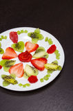 Sliced kiwi and strawberries lying in neatly placed pattern on white plate, as senn from above Royalty Free Stock Image