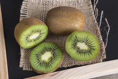 Sliced kiwifruits. Liced kiwifruits on black chalkboard top view Stock Photography