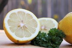 Sliced lemon. Fresh sliced lemon on cutting board complimented with parsley Stock Photos