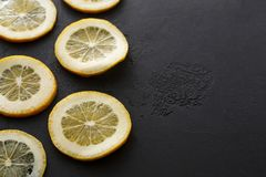Sliced lemon on black background, copy space Stock Images