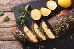 Sliced lemon cake with chocolate glaze and zest close-up. horizo Royalty Free Stock Photography