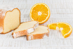 Sliced lemon cake with some fresh orange fruits on a wooden tabl Stock Images