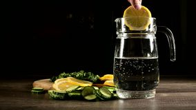 Sliced lemon cucumbers and mint leaves on a wooden cutting board next to a glass carafe with sparkling water. Male hand. Throwing slices of lemon in a glass of stock footage