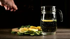 Sliced lemon cucumbers and mint leaves on a wooden cutting board next to a glass carafe with sparkling water. Male hand. Throwing cucumber slices into a glass stock footage