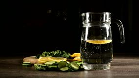Sliced lemon cucumbers and mint leaves on a wooden cutting board next to a glass carafe with sparkling water. Male hand. Throwing slices of lemon in a glass of stock video