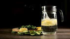 Sliced lemon cucumbers and mint leaves on a wooden cutting board next to a glass carafe with sparkling water. Male hand. Throwing slices of lemon in a glass of stock video footage