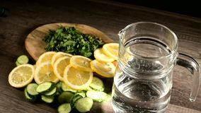 Sliced lemon cucumbers and mint leaves on a wooden cutting board next to a glass carafe with sparkling water.  stock footage