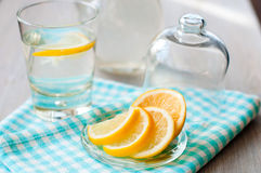 Sliced lemon with a glass of water. Sliced lemon with water in the glass Royalty Free Stock Photo