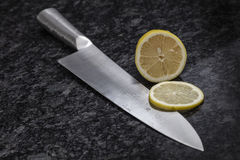 Sliced lemon and a knife on a cooking island. A sliced lemon and a sharp edged kitchen knife on a cooking island. Photo taken on October, 2016 Stock Photography