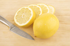Sliced lemon and knive. On wooden background Royalty Free Stock Images
