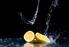 Sliced lemon in the water on black background. Fresh lemons with water splash. Dynamics of a liquid, juicy appetizing lemon and glass with splashed out water Royalty Free Stock Image