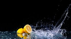 Sliced lemon in the water on black background. Fresh lemons with water splash. Dynamics of a liquid, juicy appetizing lemon and glass with splashed out water Royalty Free Stock Images