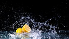 Sliced lemon in the water on black background. Fresh lemons with water splash. Dynamics of a liquid, juicy appetizing lemon and glass with splashed out water Stock Image