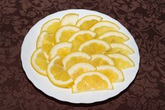 Sliced lemon on white plate. Brown background cutting slices citrus fruit sour yellow food fresh organic ripe board juicy natural raw tangy tropical zesty royalty free stock images