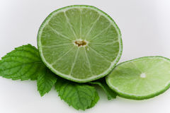 A sliced lime. A lime on a mint leaf, isolated on a white background Royalty Free Stock Photo