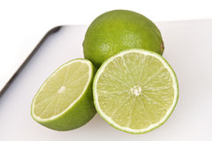 Sliced lime on a cutting board. A sliced lime on a cuttinboard with thite background Stock Images