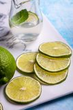 Sliced lime and juice. On ceramic platter closeup stock photos