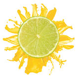 Sliced lime splash with orange juice isolated royalty free stock images
