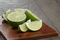 Sliced limes on wooden board Royalty Free Stock Photos